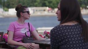 Unga flickor sitter på terrass av restaurangen på sjösidan solglasögon vänner relax arkivfilmer