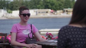Unga flickor sitter på terrass av restaurangen på sjösidan tala vänner relax stock video
