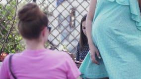 Unga flickor sitter på terrass av restaurangen tala gravid kvinna ferier arkivfilmer