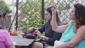Unga flickor sitter på terrass av restaurangen tala Gravid kvinnatagandeselfie arkivfilmer