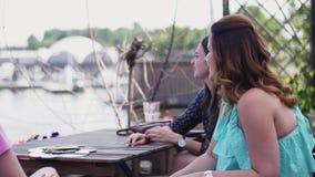 Unga flickor sitter på terrass av restaurangen tala seafront ferier Vatten arkivfilmer