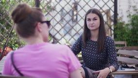 Unga flickor sitter på terrass av restaurangen tala semester relax ferier stock video