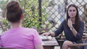 Unga flickor sitter på terrass av restaurangen tala tabell relax ferier lager videofilmer