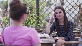 Unga flickor sitter på terrass av restaurangen tala vänner relax ferier lager videofilmer