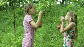 Unga flickor som blåser utomhus- såpbubblor arkivfilmer