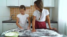 Unga flickor som förbereder funktionsduglig yttersida för deg som knådar fördelande mjöl på den mörka tabellen i kök stock video
