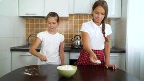 Unga flickor som förbereder funktionsduglig yttersida för deg som knådar fördelande mjöl på den mörka tabellen i kök lager videofilmer