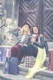 Unga flickor som grillar, når att ha shoppat Två flickor som sitter på st Royaltyfri Foto