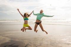 Unga flickor som hoppar på stranden Arkivbilder