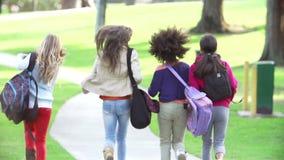 Unga flickor som kör i ultrarapid i väg från kamera parkerar in stock video