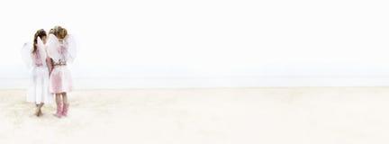 Unga flickor som kläs som feer på stranden Royaltyfria Foton