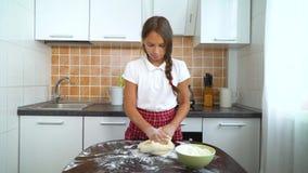 Unga flickor som knådar deg på den mörka tabellen i kök arkivfilmer