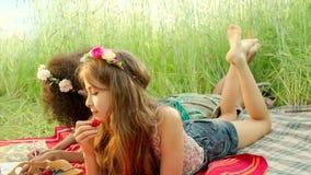 Unga flickor som ligger på deras stomaches och flyttning deras fot arkivfilmer