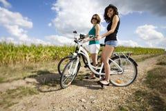 Unga flickor som rider en cykel Arkivbild