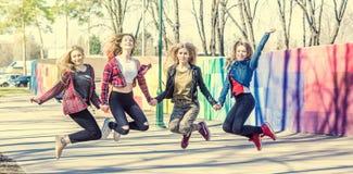 Unga flickor som rymmer händer och tillsammans hoppar fotografering för bildbyråer