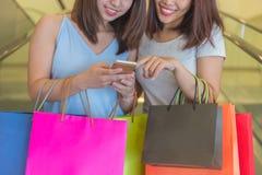 Unga flickor som rymmer shoppingpåsen och kontrollerar online-avtal fotografering för bildbyråer