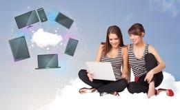 Unga flickor som sitter på molnet som tycker om molnnätverksservice Arkivfoton
