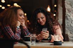 Unga flickor som sitter på kafét och använder telefonen Arkivfoton