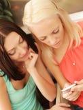 Unga flickor som ut kontrollerar deras nya mobilephone royaltyfri bild