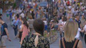 Unga flickor står på en upptagen gata arkivfilmer