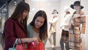 Unga flickvänner med påsar som nära står, shoppar fönstret med den nya samlingen av kläder och diskuterar köp i galleria arkivfilmer