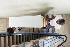 Unga flyttkarlar som bär hyllan, medan klättra moment arkivbild