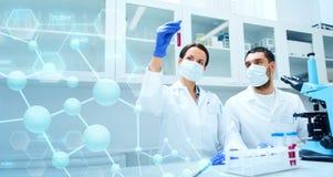 Unga forskare som gör provet eller forskning i labb royaltyfri bild