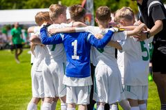 Unga fotbollfotbollspelare i sportswear LagledareMotivating Kids In sportar Royaltyfri Bild