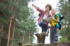 Unga fotvandra par med översikten som diskuterar över riktning i skog Royaltyfri Fotografi