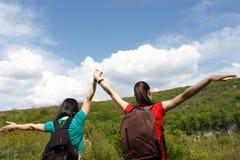 Unga fotvandrareflickor med ryggsäcken som tycker om och ser till himlen med moln Arkivfoto