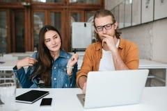 Unga fundersamma studenter som sitter i salong och arbete samman med bärbara datorn och mobiltelefonen på tabellen Nätt flicka royaltyfri bild