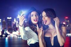 Unga galna flickvänner som tar selfie på natten i stad Royaltyfri Fotografi