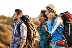 Unga gladlynta handelsresande med förvånade ryggsäckar och att le som går i kanjon royaltyfri bild