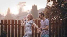 Unga gladlynta par på trädgården och att ha gyckel tillsammans på solnedgång Gladlynt man- och kvinnadans utanför