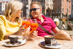 Unga gladlynta par som dricker Aperol, Spritz coctailen i kafé Royaltyfri Bild