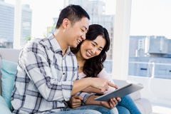 Unga gladlynta par som ser den digitala minnestavlan Arkivfoto