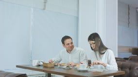 Unga gladlynta par som tycker om affärslunch på restaurangen arkivfoton
