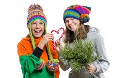 Unga gladlynta tonårs- flickor som har gyckel med julgodisrottingar, i vinterluvor som isoleras på vit bakgrund royaltyfri foto