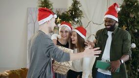 Unga gladlynta vänner i jultomtenhattar som firar jul, står för julträdet som rymmer närvarande askar och arkivfilmer