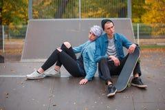 Unga grabb- och flickaskateboarders, utomhus på en ljus höstdag royaltyfria foton