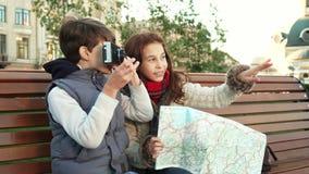 Unga grabbar sitter på en bänk och tar bilder av sikt fotografering för bildbyråer