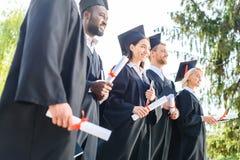 unga graderade studenter, i uddar och att rymma för hattar royaltyfri foto
