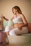 Unga gravid kvinnamaskinskrivningmeddelanden på den smarta telefonen royaltyfri foto