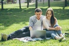 Unga gulliga par genom att använda en bärbar dator i parkera på en solig dag royaltyfri fotografi