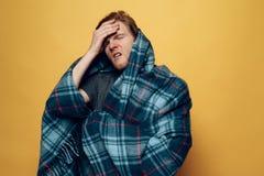 Unga Guy Wrapped i pläd som hostar med huvudvärk arkivbild