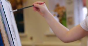 Unga händer av konstnären, frugankonstnären Paints en kanfas med borsten och att sitta en Ttable och att dra på kanfas behandling lager videofilmer