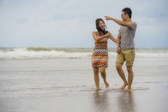 Unga härliga asiatiska kinesiska par som tillsammans går på den lyckliga förälskade tyckande om ferien för strand Royaltyfri Foto