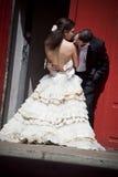 Unga härliga brud- par som kysser mot röd byggnad Arkivfoto