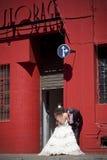 Unga härliga brud- par som kysser mot röd byggnad Arkivbilder