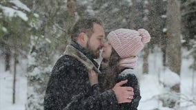 Unga härliga caucasian par som tillsammans kysser under trendiga millennials för en insnöad vinterskog som har gyckel lager videofilmer